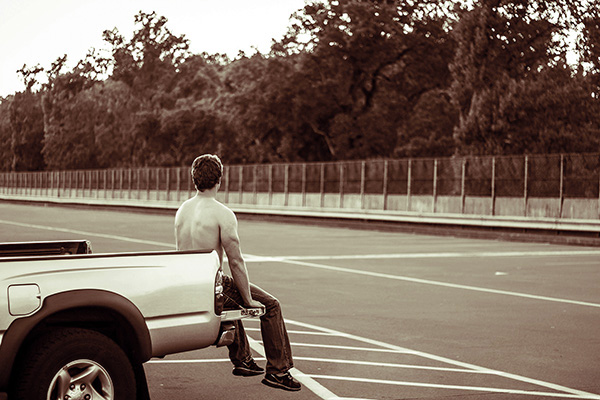 boy sitting on back of truck